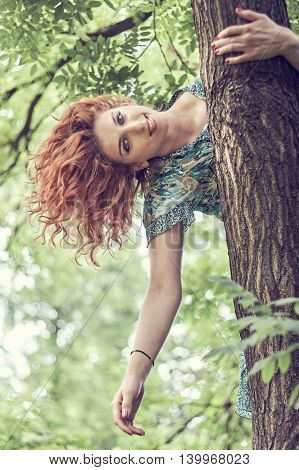 Girl with red hair and blue floral dress hanging from tree. Copy space