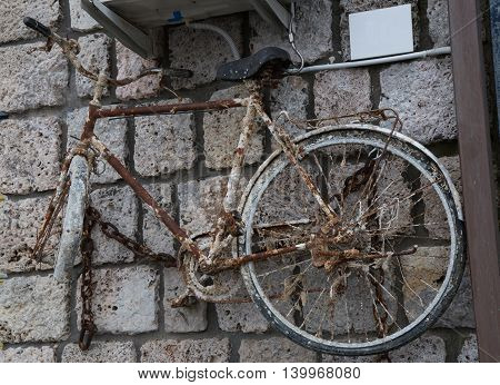 Old bicycle with rust stuck to the wall