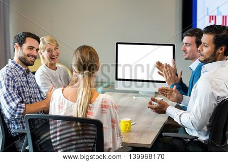 Coworkers applauding a colleague during a video conference in the conference room