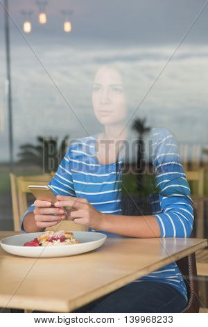 Woman holding mobile phone in cafeteria