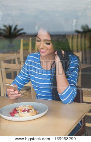 Woman text messaging on mobile phone in cafeteria