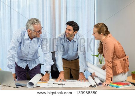 Businesswoman and coworker discussing blueprint in the office