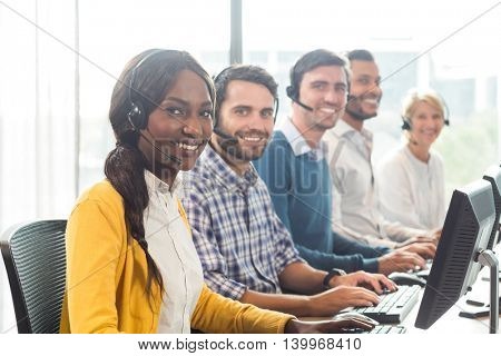 Portrait of colleagues working at their desk with headset in the office