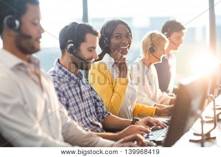 Team working on computer with headset while a colleague smiling at camera in the office