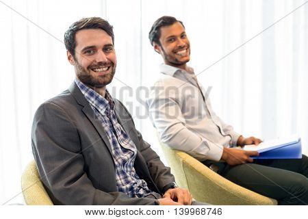 Portrait of men smiling at camera while sitting in the office