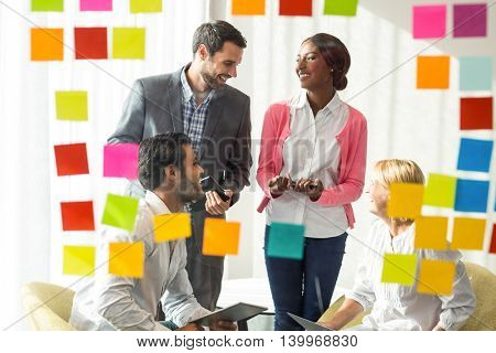 Business people discussing over adhesive notes on glass wall in the office