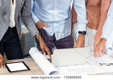 Mid section of business people with blueprint on the desk using laptop in the office