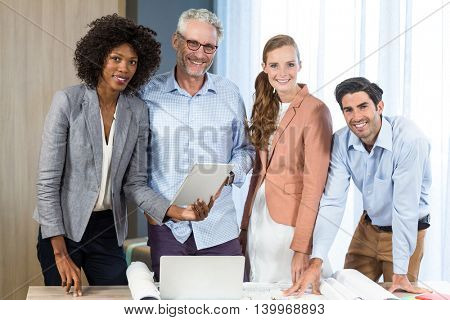 Portrait of businesswoman and coworker with blueprint on the desk in the office