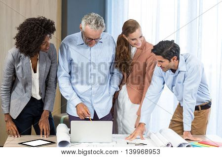 Businesswoman and coworker discussing blueprint on the desk using laptop in the office
