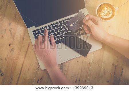 Online paymentMan's hands holding a credit card and using laptop for online shopping with vintage filter effect