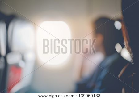 Abstract blur of woman looks out the window of an flying airplane. vintage filter effect