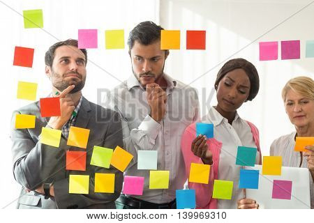 Business people looking at adhesive notes on glass wall in the office