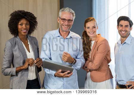 Portrait of smiling business people standing together with laptop in office