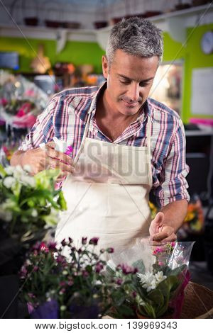 Male florist spraying water on flowers at his flower shop