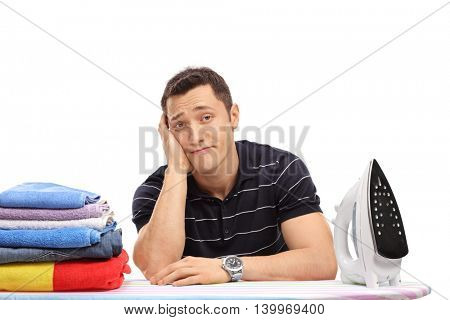 Bored young guy sitting behind an ironing board and looking at the camera isolated on white background