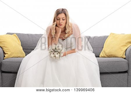 Worried young bride in a white wedding dress sitting on a sofa and contemplating isolated on white background