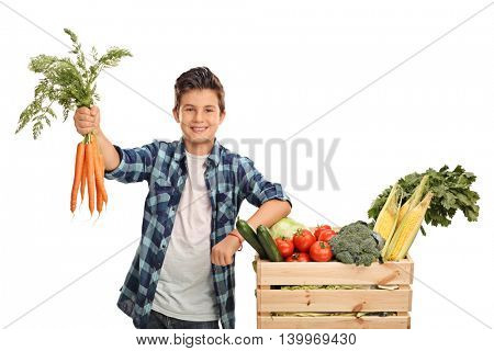 Joyful kid holding a bunch of carrots and posing next to a crate full of vegetables isolated on white background