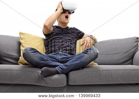 Excited young man looking in VR goggles seated on a gray sofa isolated on white background