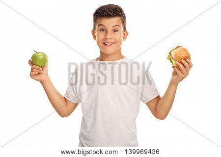 Little boy holding an apple in one hand and a sandwich in the other isolated on white background