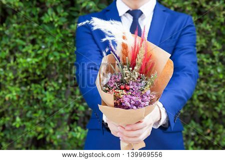 Young man in fashionable suit holding hipster hand-made bouquet in green bushes nature background