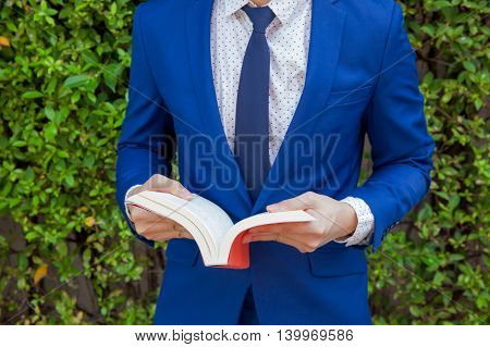 Young businessman reading book in green nature background.