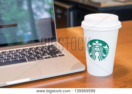 OSAKA JAPAN JUL 09 2016: A tall Starbucks coffee and laptop computer on wooden desk.