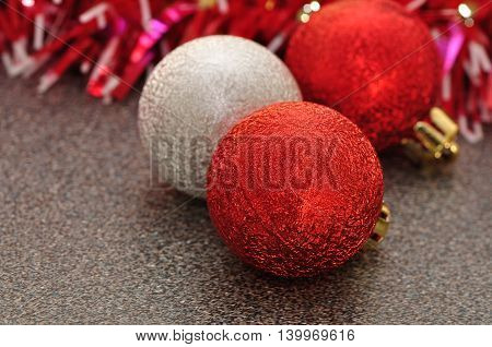 Red and silver Christmas tree baubles on a grey background