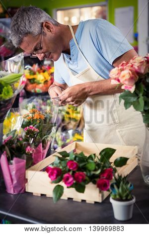 Male florist preparing bouquet of flower at his flower shop