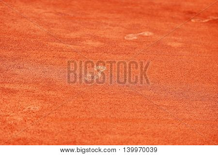 Detail with sport shoe footprints on a tennis clay court