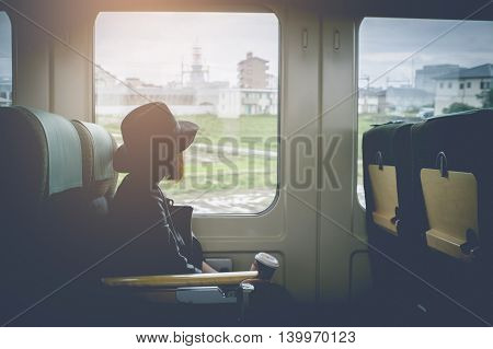 Enjoying travel. Young pretty woman traveling by the japan classic train sitting near the window. vintage filter.