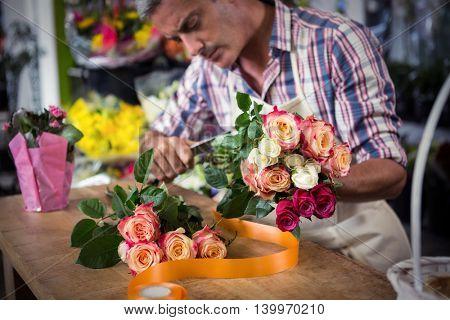 Male florist preparing bouquet of flower at his flower shop