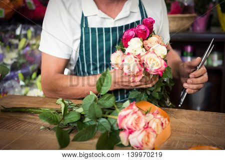 Mid section of male florist holding bunch of roses and shears at his flower shop