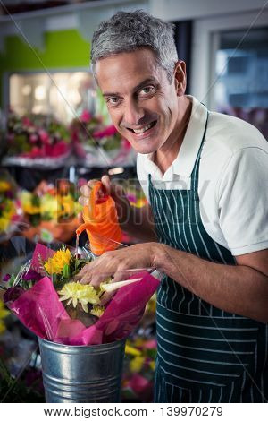 Portrait of male florist watering flowers with watering can at his flower shop