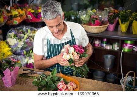 Male florist holding bunch of roses at his flower shop