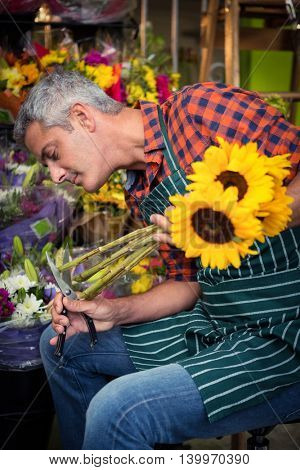 Male florist trimming stems of flowers at his flower shop