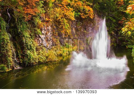 Dancing fountain in a quiet pond. Autumn day in the park. Butchart Gardens on Vancouver Island, Canada