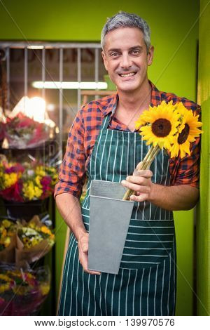 Portrait of male florist holding flower vase at his flower shop