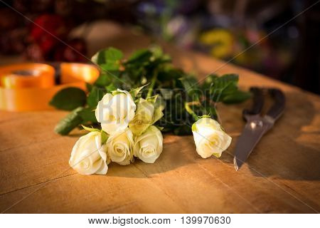 Close-up of bunch of roses with shears and poly ribbon on the wooden table at a flower shop