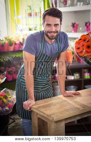 Portrait of male florist leaning on a wooden table at his flower shop