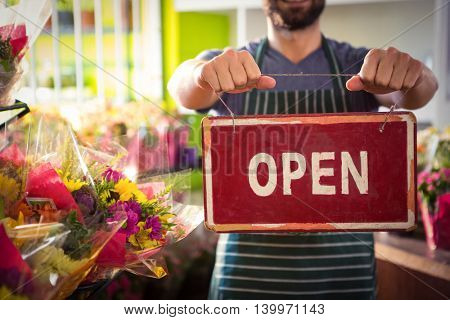 Mid section of male florist holding open signboard at his flower shop
