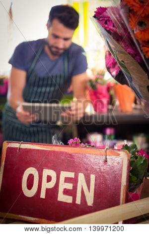 Close-Up of open signboard while of male florist using digital tablet in background at his flower shop