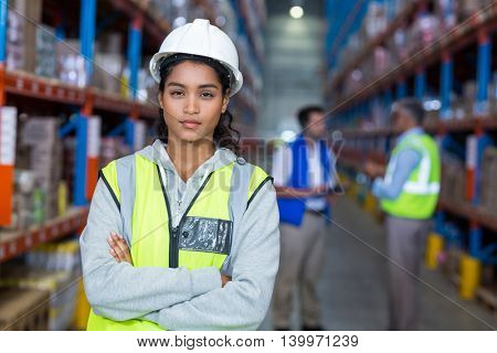Worker crossing arms in warehouse