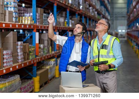 Worker colleague looking up in warehouse