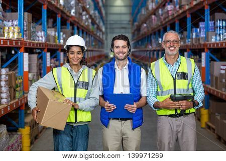Smiling group of workers looking at camera in warehouse