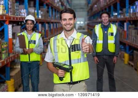 Worker in warehouse with thumb up wearing yellow safety vest