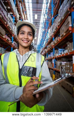 Smiling female worker holding clipboard in warehouse