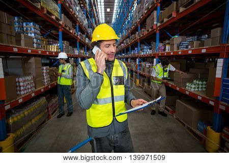 Worker using phone in warehouse