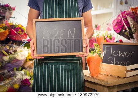 Mid section of male florist holding open sign on slate at his flower shop