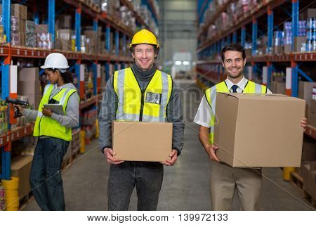 Workers looking at camera while holding box in warehouse