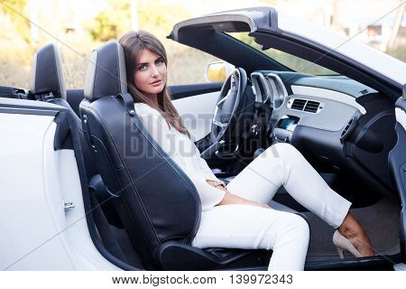 business Lady sits in white cabriolet travel